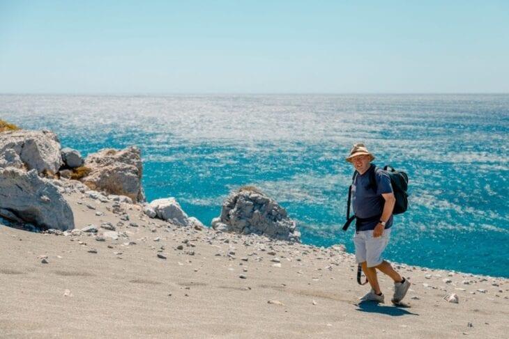 Starszy mężczyzna spacerujący po plaży na Krecie