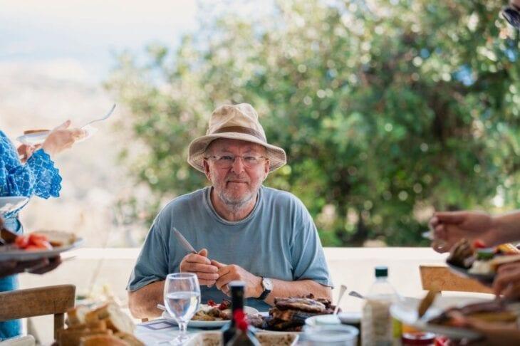 Uśmiechnięty senior na Krecie jedzący lunch
