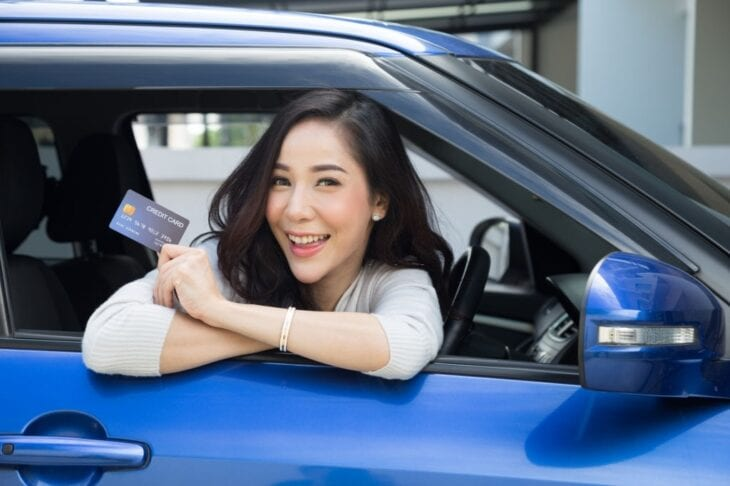 Woman holding a credit card in car