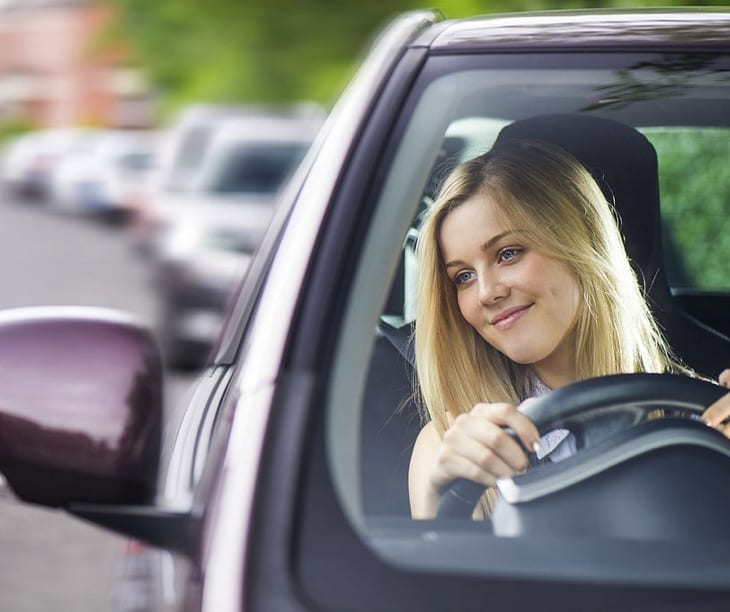 Blonde young girl driving in Crete
