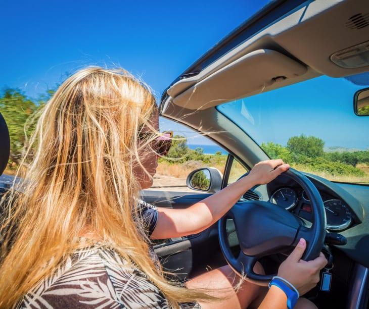 Blondes Mädchen am Steuer eines Mietwagens auf Kreta