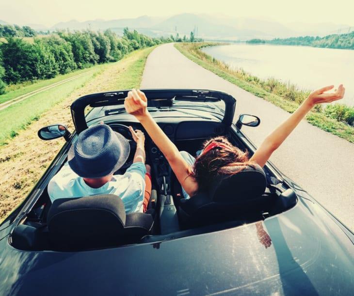 Couple Riding a cabriolet Car