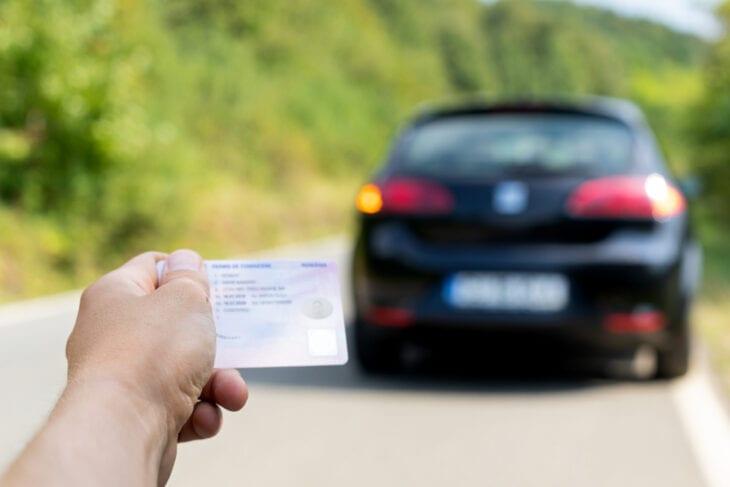 Κρατώντας το δίπλωμα οδήγησης κοντά στο ενοικιαζόμενο αυτοκίνητο