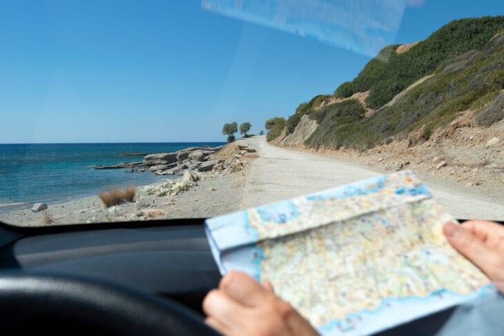 Turyści w wynajętym samochodzie przeszukujący mapę