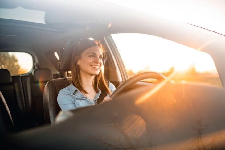 Giovane ragazza alla guida di un'auto a noleggio